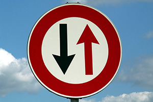 Road sign pointing both ways, one black arrow and one red
