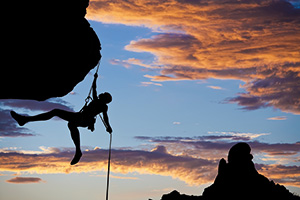 Photo of a silhouette person rock climbing whilst the sun is setting
