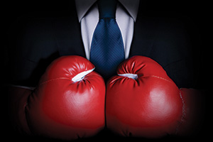 Businessman wearing a suit and red boxing gloves