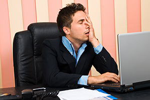 Stressed businessman with problems on laptop holding face in his hand
