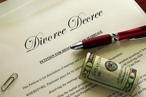 A picture of a divorce decree with a pen and roll of US dollars on top of it