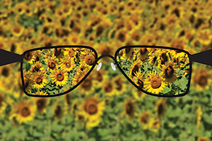 Eye glasses helping to see a field of sunflowers clearer