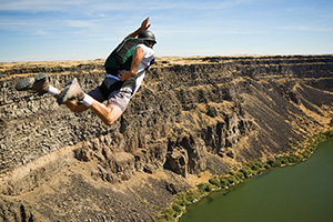 Base jumper jumping off a cliff