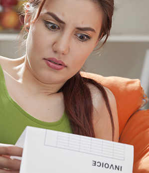 Woman shocked holding bill or invoice