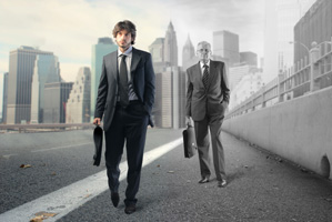 Photo of a young businessman and an older businessman walking on the same street to work