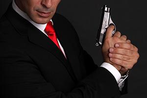Photo of a man with a gun imitating James Bond