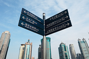 Photo of a signpost with Shanghi skyline of the Lujiazui financial center at daytime