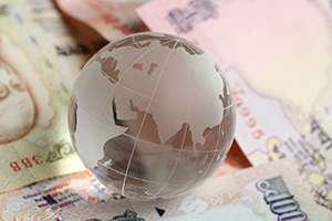Photo of a glass globe on top of Indian Rupees