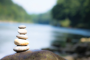 Photo of stones stacked on top of each other to represent team work balance