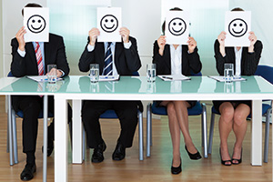Business executives with smiley faces in front of their faces