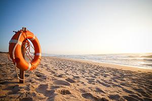 Sandy beach with lifebuoy