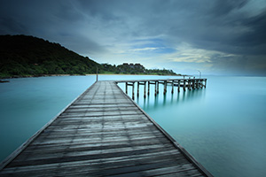 Wooden pier above blue seascape