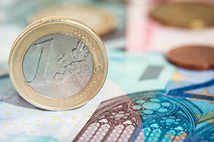Euro coin balancing on Euro notes
