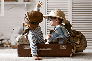 Kids playing in suitcase using it as a plane