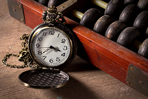 Old pocket watch next to an old abacus