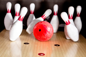 Bowling ball knocking down pins