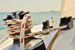 Red and White rope wrapped around winch of sailboat