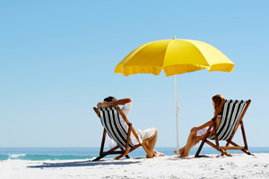 Couple on beach in deck chairs