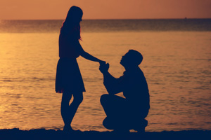 Man on one knee, proposing to a woman during sunset