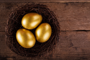 Three golden eggs in a nest