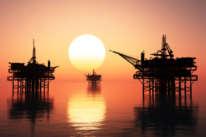 Oil rigs out at sea in the sunset