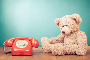 Soft toy teddy bear sitting next to old fashioned telephone