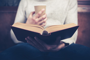 Man reading book with coffee