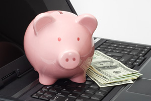 Piggy bank sitting on a laptop with money