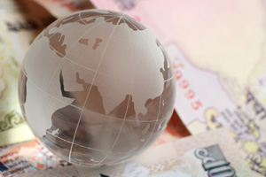 Glass globe sitting on Indian rupees