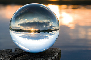 Glass ball looking out over a lake at sunset