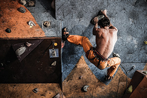 Muscular man practicing rock climbing
