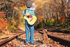 Little boy with guitar and dog walking along the railroad