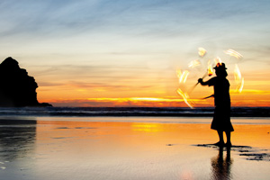 Fire juggler practising on a beach during sunset