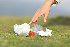 Woman's hand picking up rubbish