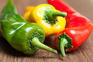 Three peppers, green, yellow and red.