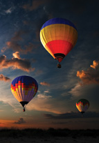 Colourful hot air balloons flying at sunset