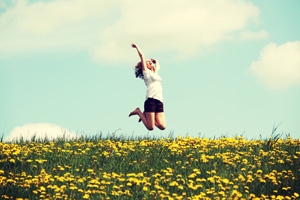 Woman jumping with joy in a field on a beautiful day