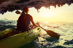 Woman kayaking out of a water cave