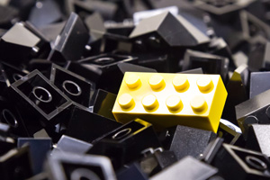 Pile of black lego with a single yellow piece