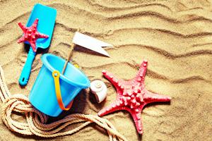 Bucket and spade on sandy beach