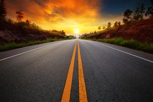 Straight road heading towards sunset