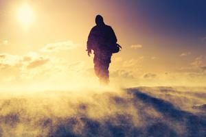 Sillhoutte of walker on top of a mountain