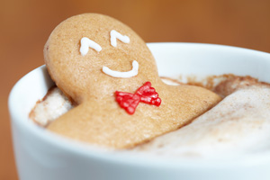 Happy gingerbread man sitting in hot drink