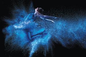 Young ballet dancer jumping through blue powder