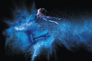 Young ballet dancer jumping through blue powder