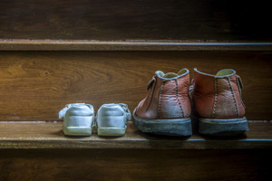 Father and childs shoes sitting on stairs