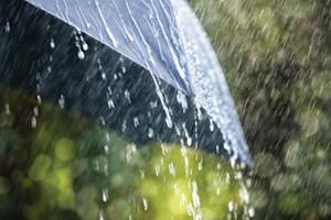 Rain pouring from a black umbrella