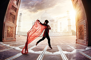 Woman with red scarf dancing near the Taj Mahal in India