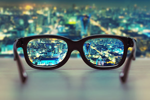 Glasses looking over city scape at night in focus