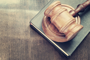 Gavel and legal book on wooden table